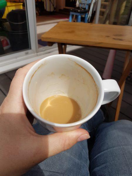 halb leere Kaffeetasse in der Hand