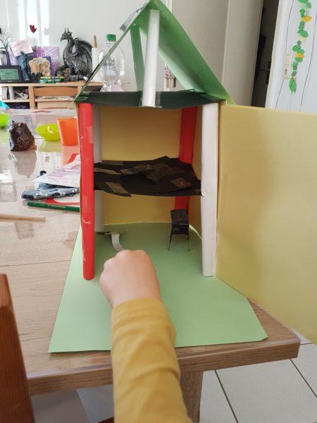 gebasteltes Haus mit einer Hand vom Kind