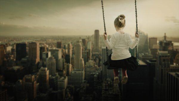 Mädchen auf einer Schaukel mit dem Blick auf eine Großstadt